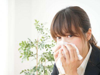 アレルギー性鼻炎で鼻をかむ女性